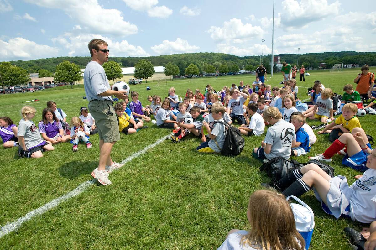 Colgate's head soccer coach speaks to participants of a youth soccer camp on the university's campus.