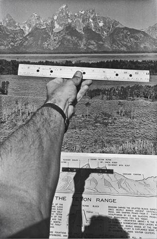 Arm holding ruler out to horizon with mountains