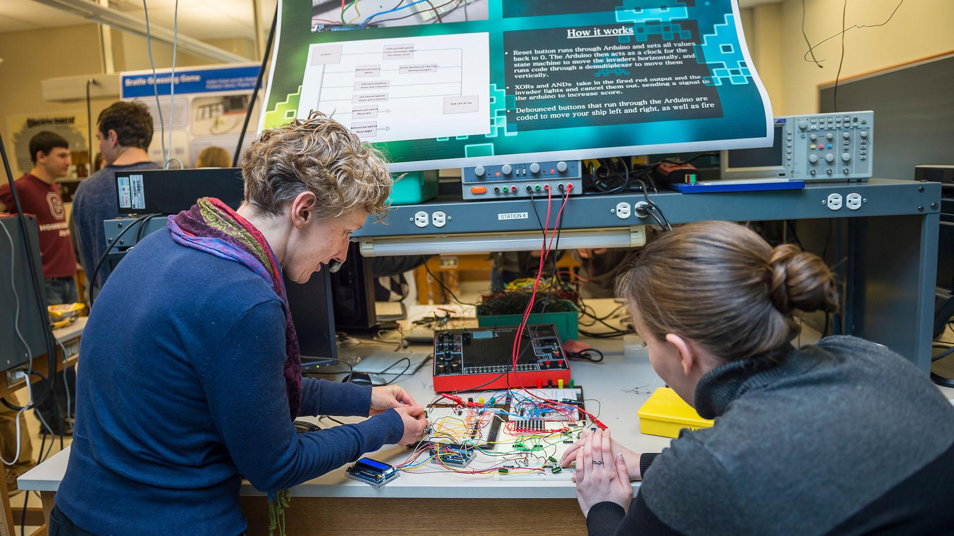 Associate Professor of Physics and Astronomy Beth Parks investigates an electronic game with a physics student.