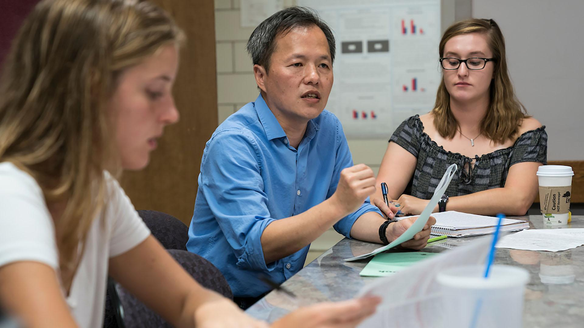 Professor Wan-Chun Liu speaks with a small group of students at a table.
