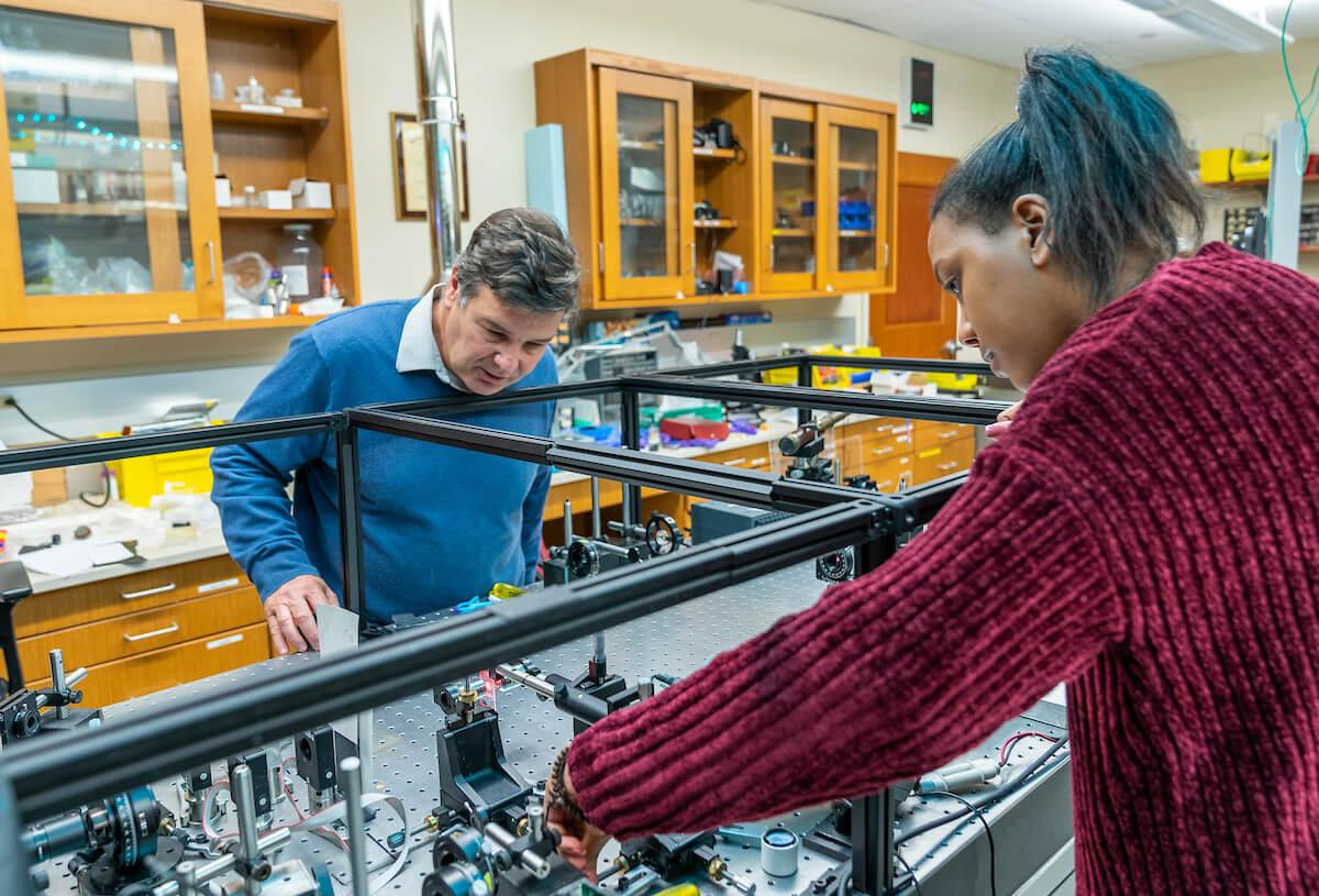 Charles A. Dana Professor of Physics and Astronomy Enrique Galvez works with a student in the Ho Science Center laser lab.