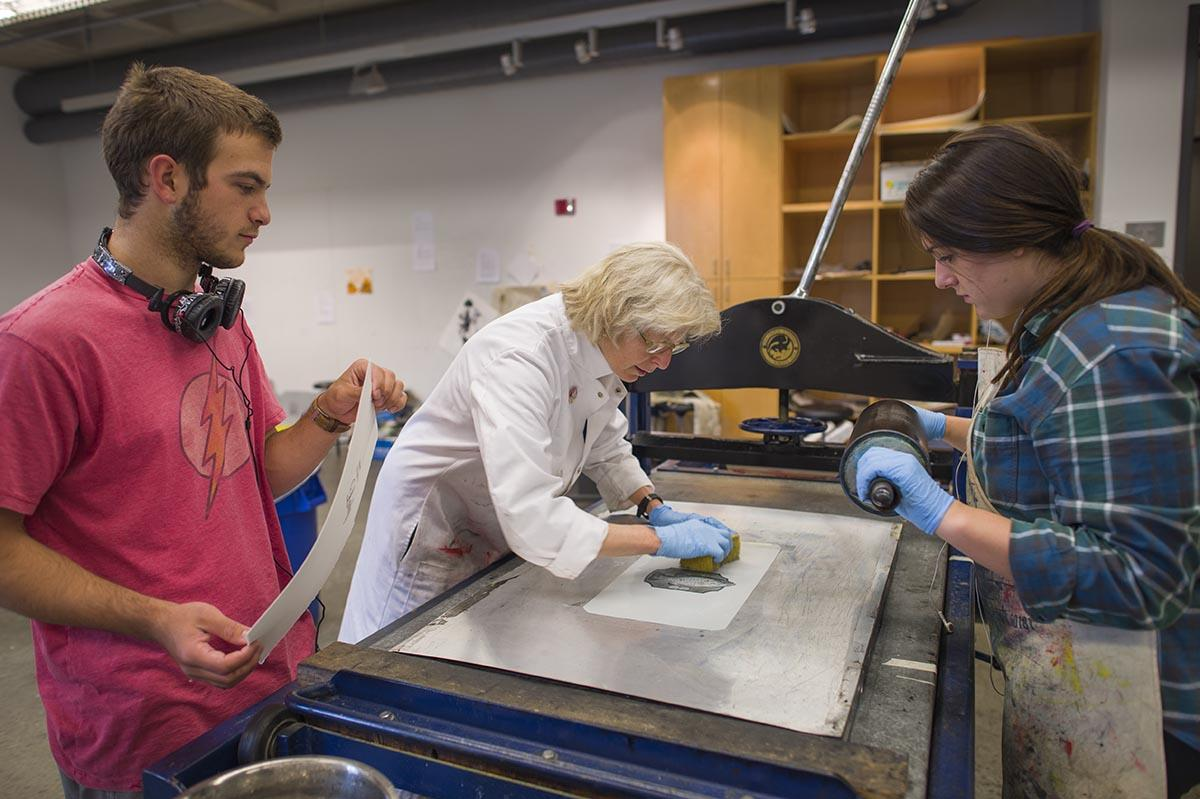 Students work with Professor Lynn Schwarzer in Little Hall's printmaking studio.