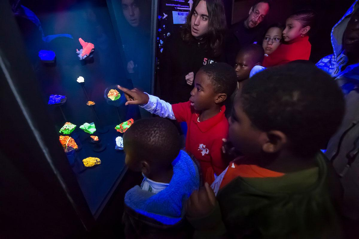 Fluorescent minerals light up visiting students faces at the Ho Tung Visualization Lab.