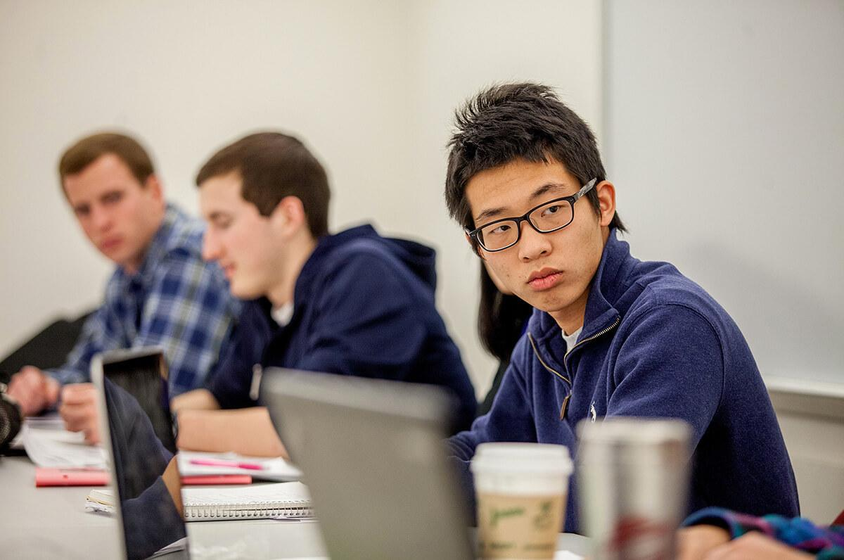 Colgate students listen in on a group discussion during a class on international finance and macroeconomics.