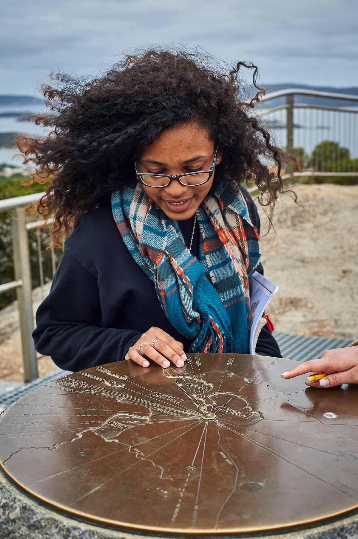 Student examines a brass map marker at a scenic overlook in Australia The Department of Geography co-sponsors, with the Environmental Studies Program, a semester-long study group at the University of Wollongong (UoW) in Australia during both the  fall and spring semesters.