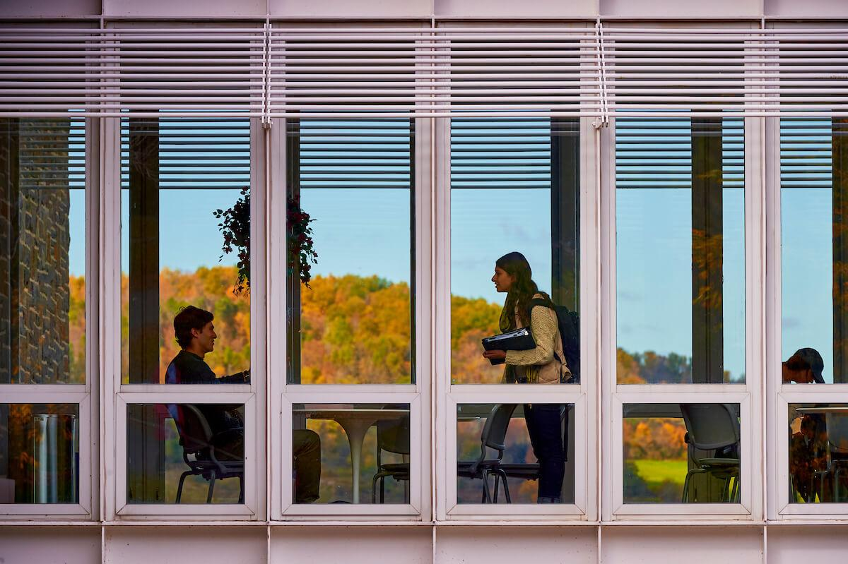 Students meet in the lounge that bridges the two wings of Persson Hall during an autumn day