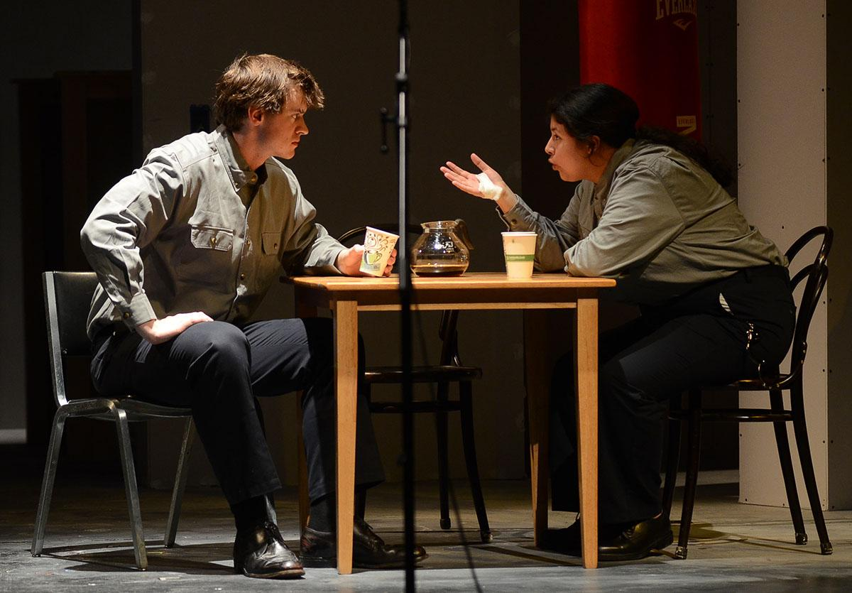 Two students perform a conversation over coffee on stage.