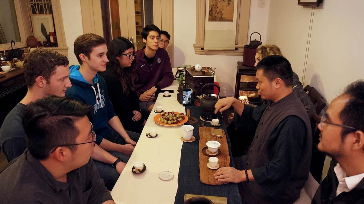Students listen attentively to man with tea set.
