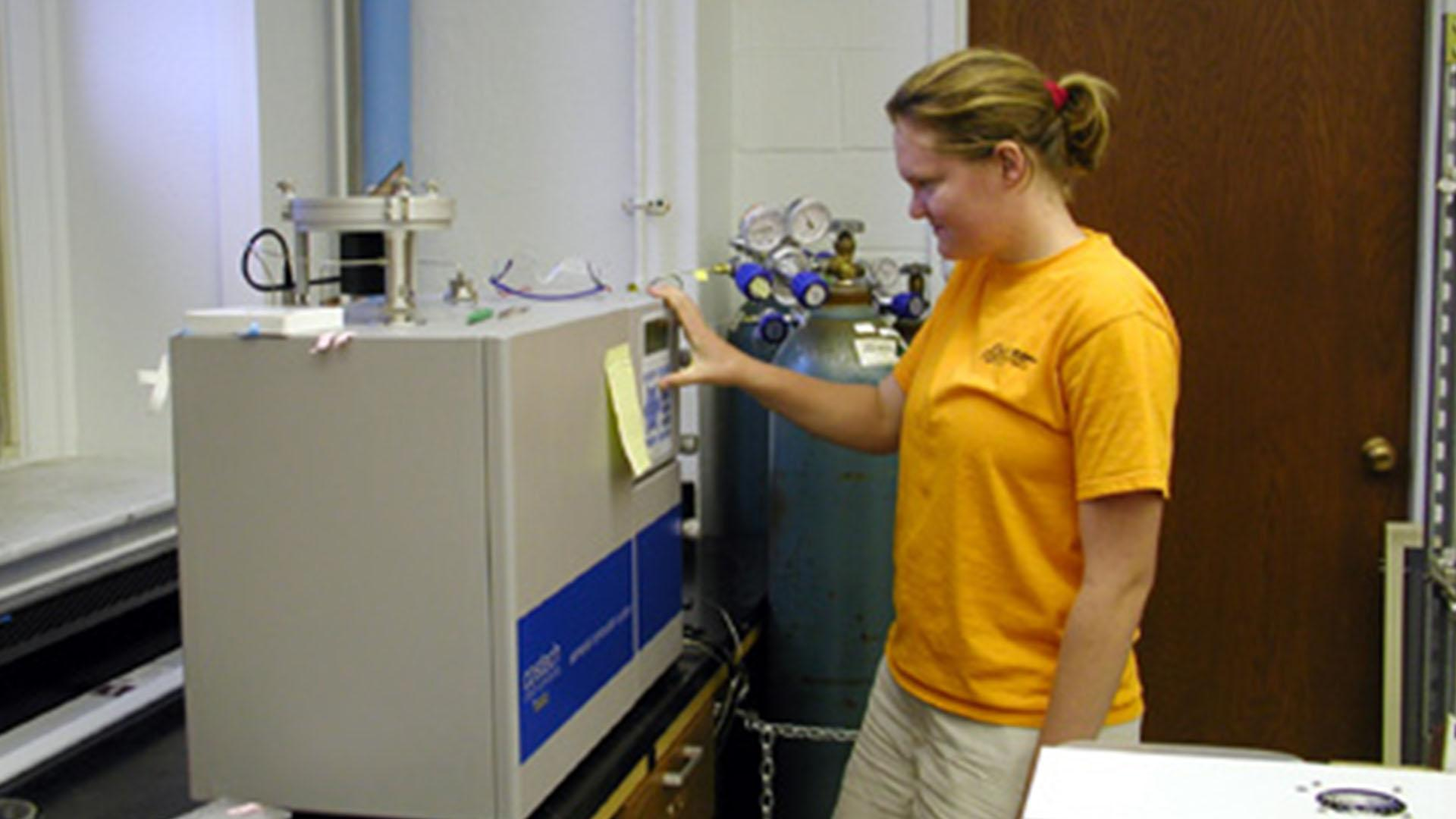 Student using stable isotope mass spectrometer in lab.