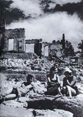People appearing to lounge, as if at a beach, but amidst the ruins of a war