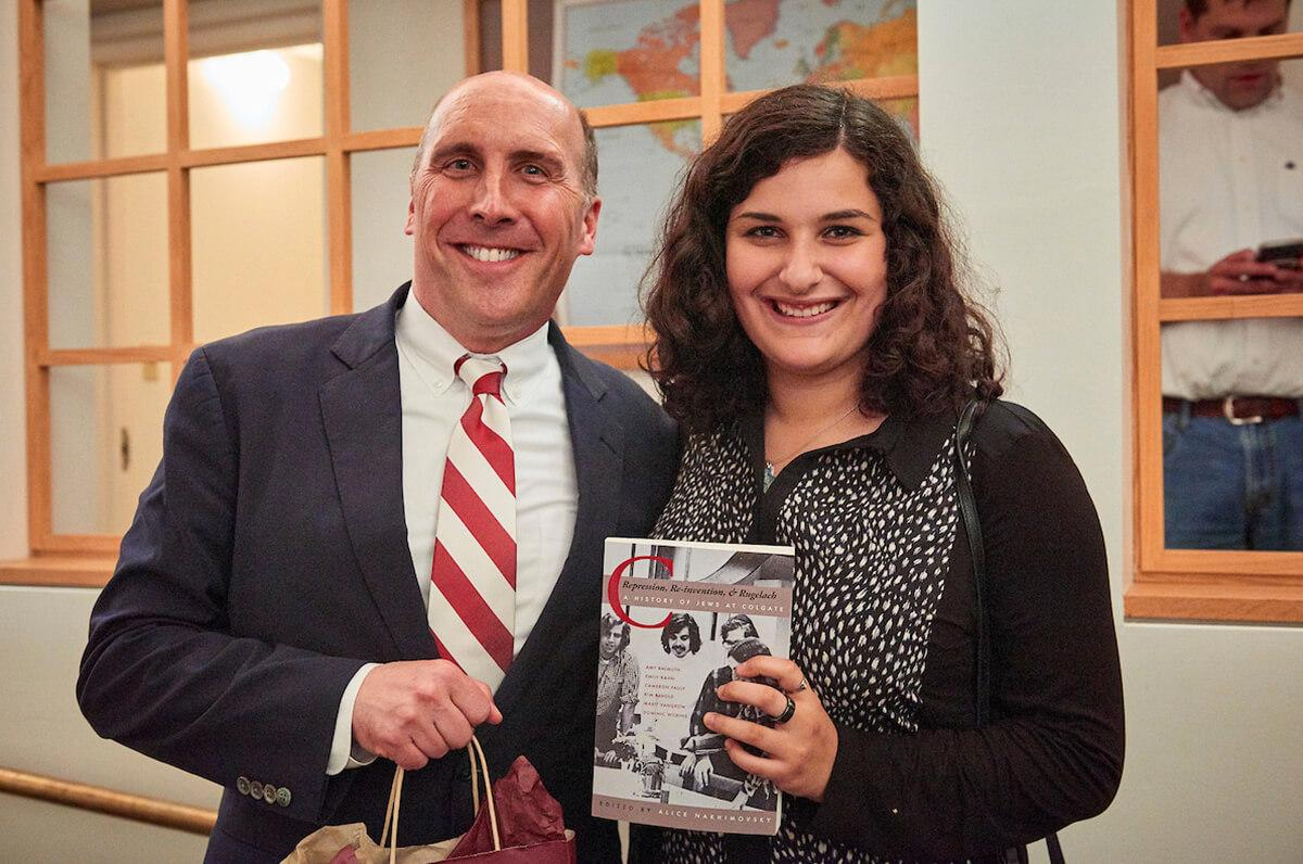 Emily Kahn '19, one of the authors of a book on the history of Jewish life at Colgate, shares the book with President Brian W. Casey.