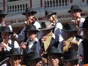A musical performance groups plays instruments in matching black hats