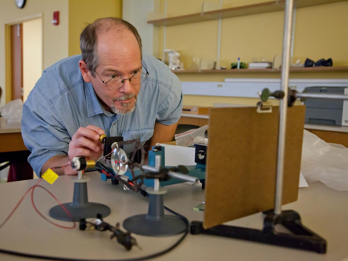 A physics professor sets up experiments for Physics 120 Lab in Ho Science Center