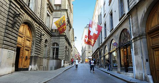 Street view of Geneva with flags and people walking.
