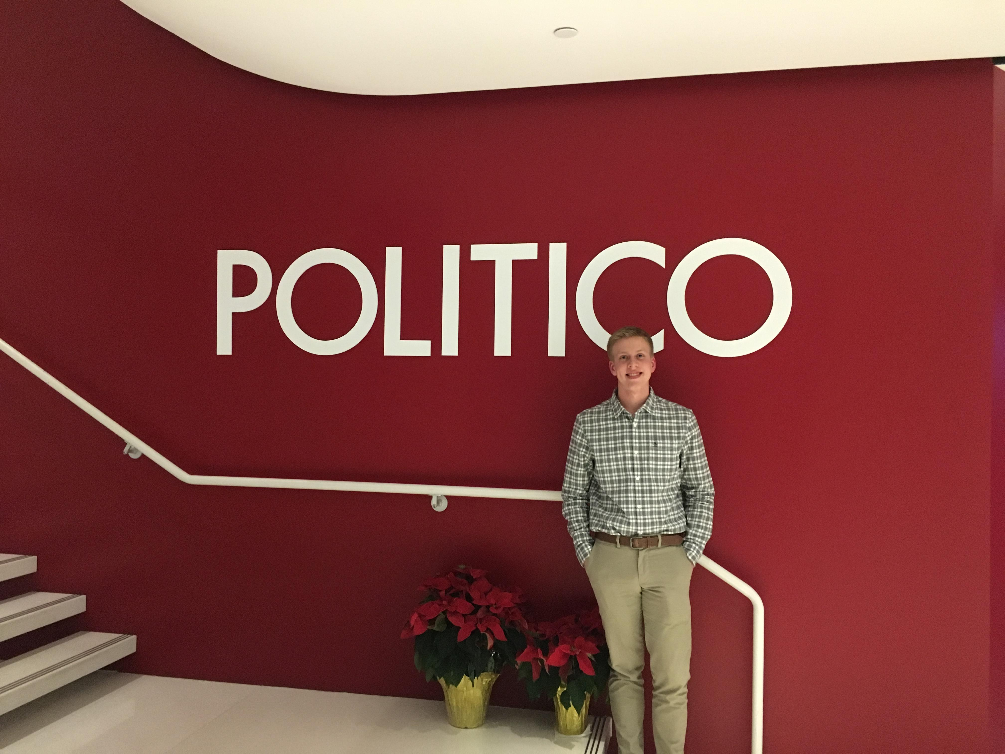 Student standing in front of the sign at Politico