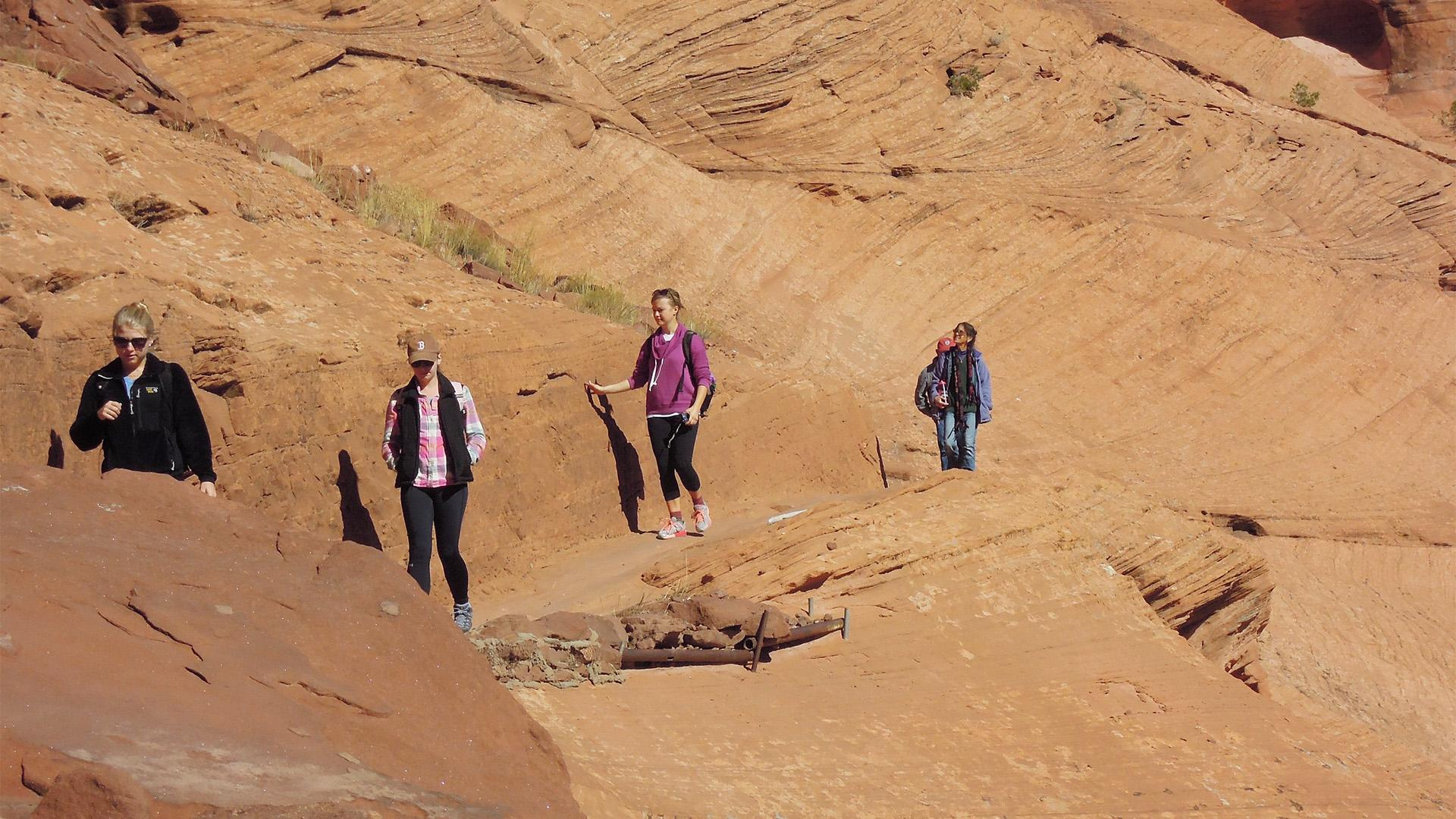 Students walk along a rock face in the western United States