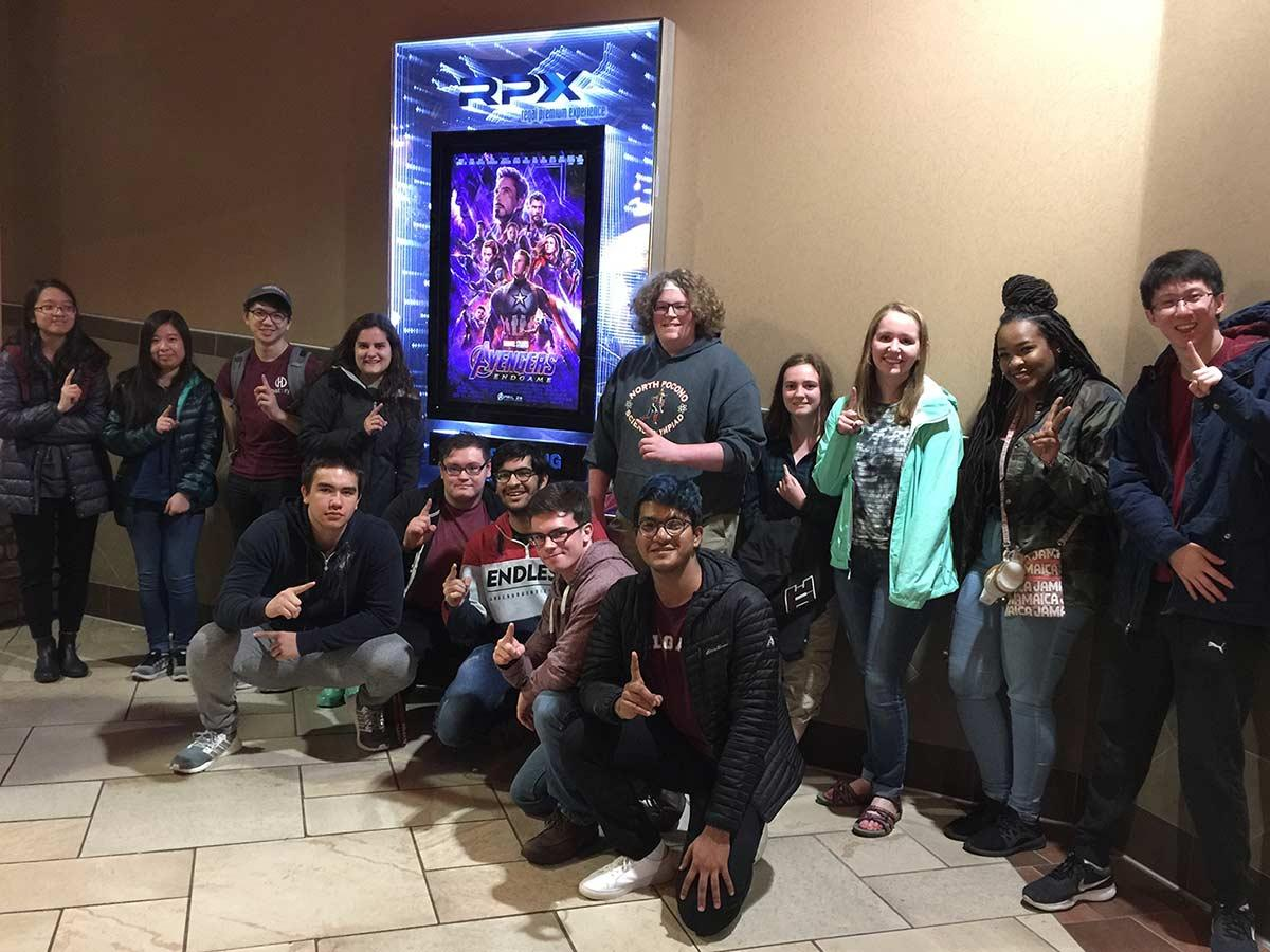 AMS students pose with the Avengers: Endgame poster outside the theater