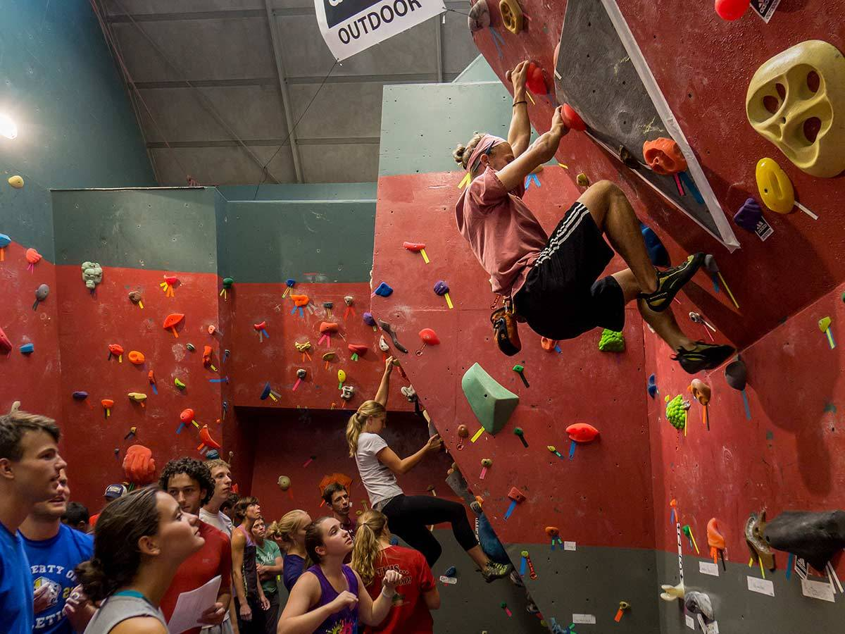 Students watch as another student scales a wall in the Angert Family Climbing Wall facility