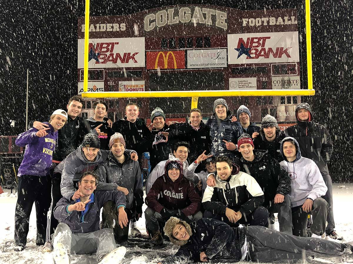 The intramural flag football champions pose for a team photo in the snow at Andy Kerr Stadium