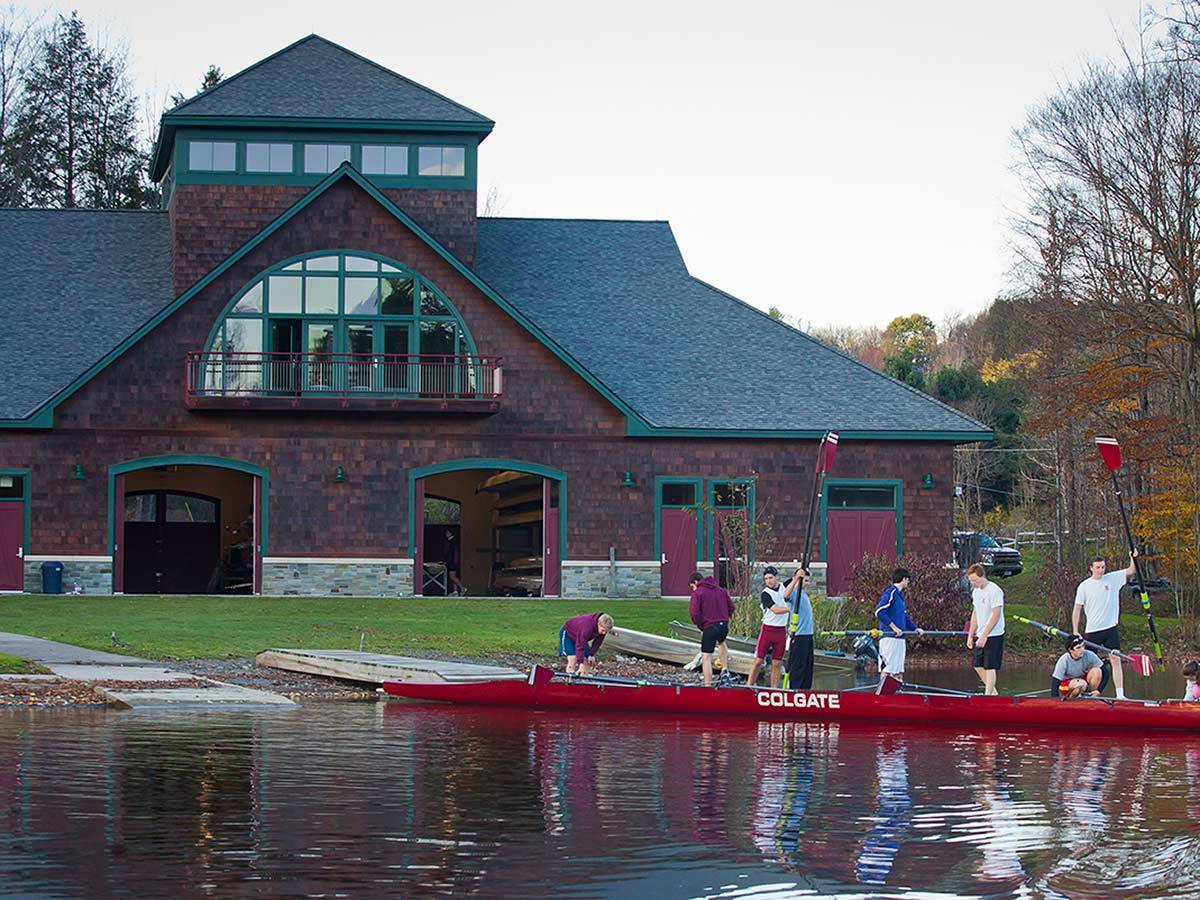The men's rowing team prepares to remove their boat from the water on the dock at Glendening Boathouse
