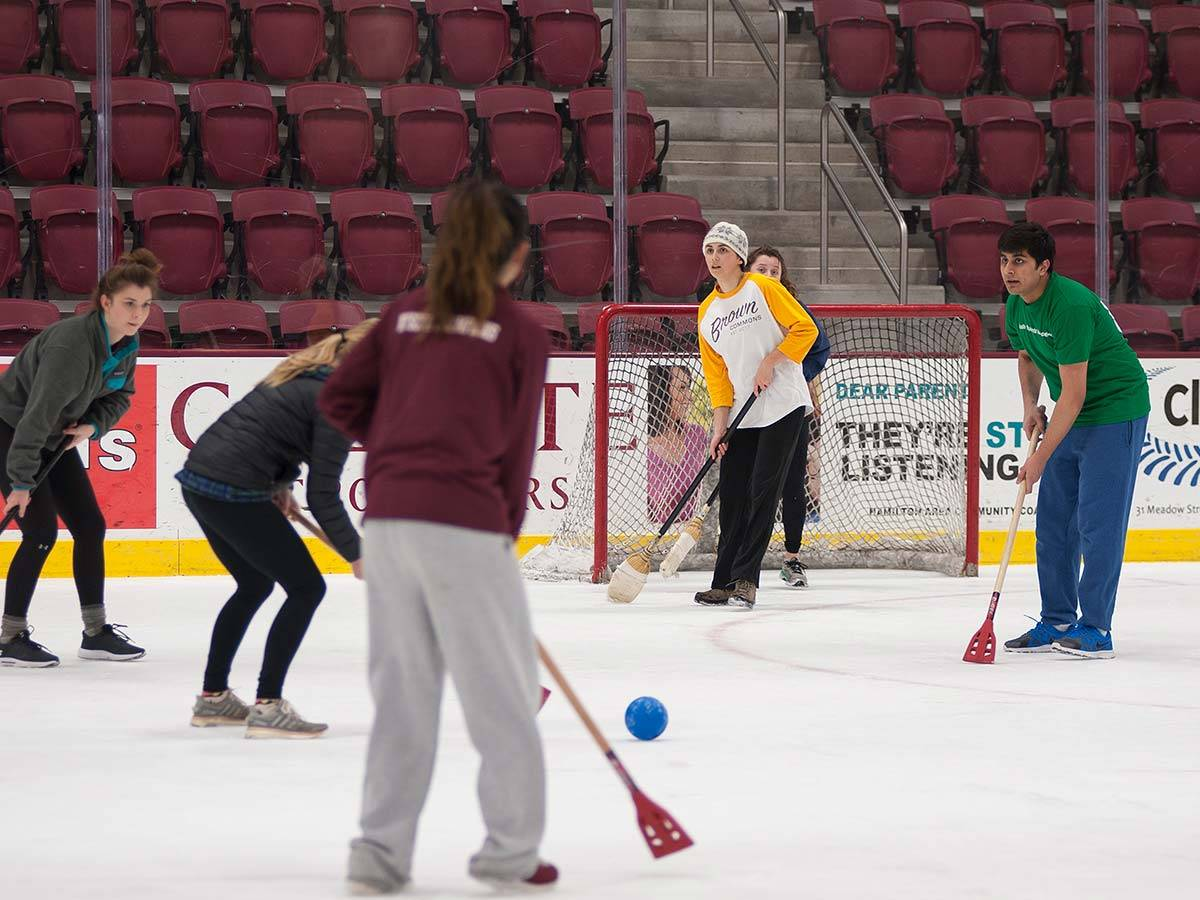 Men and women students play broomball together on Colgate's Starr Rink
