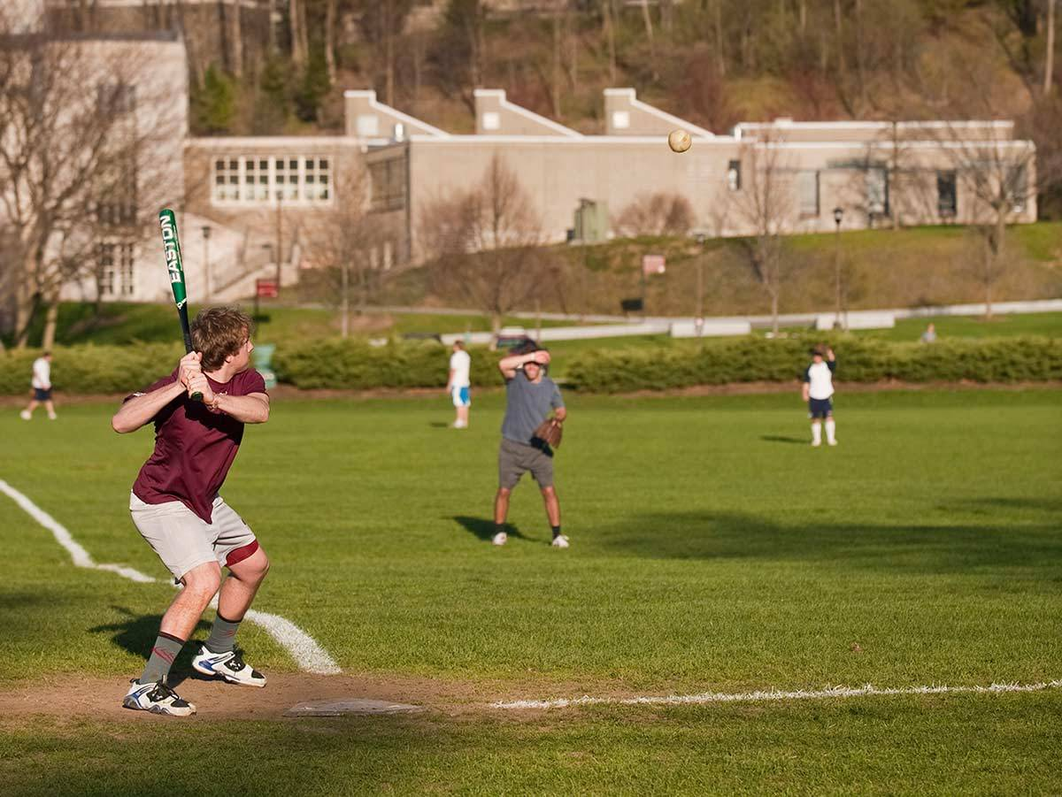 A student prepares to swing a bat at a pitched softball during an intramural game on Whitnall Field
