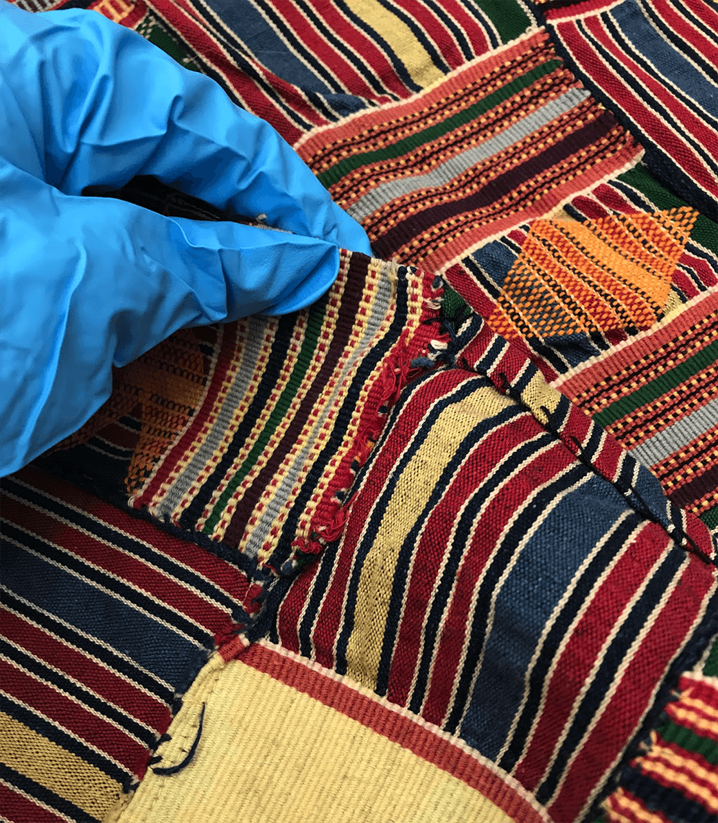 gloved hand examining patterned African textile