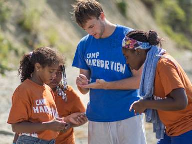 Colgate student interning with children at a beach camp