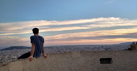 Student sitting on ledge overlooking the city of Barcelona