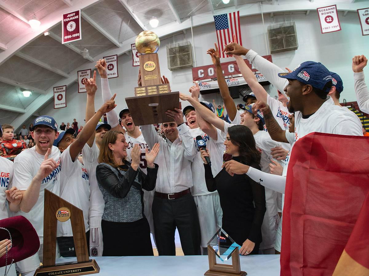 Colgate Men's Basketball coach and team holding up the 2019 Patriot League Championship trophy.