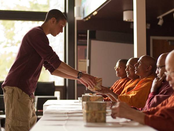 A student makes an offering to Buddhist monks.