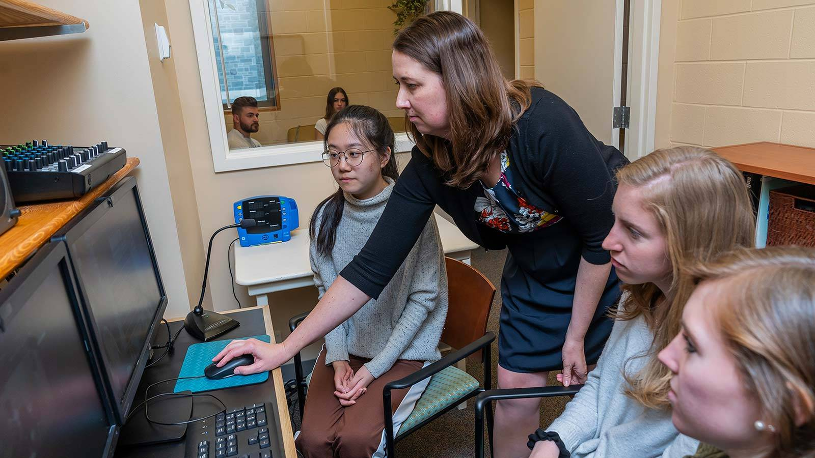 Jen Tomlinson and students work at a computer while research subjects are monitored in the background