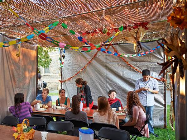 Students are celebrating Sukkot, the Jewish harvest festival, in a sukkah, which is a temporary structure that they built on the Quad.