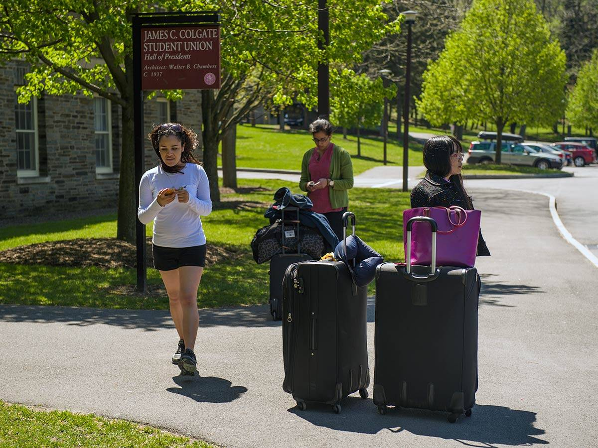 Students wait for the bus outside of James C. Colgate Hall with their luggage.