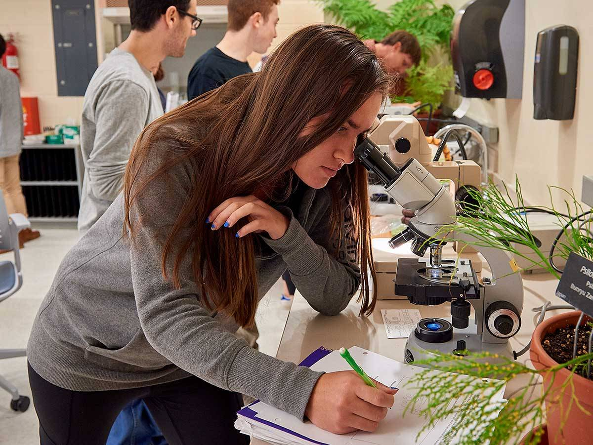 Student works at a microscope in her biology lab