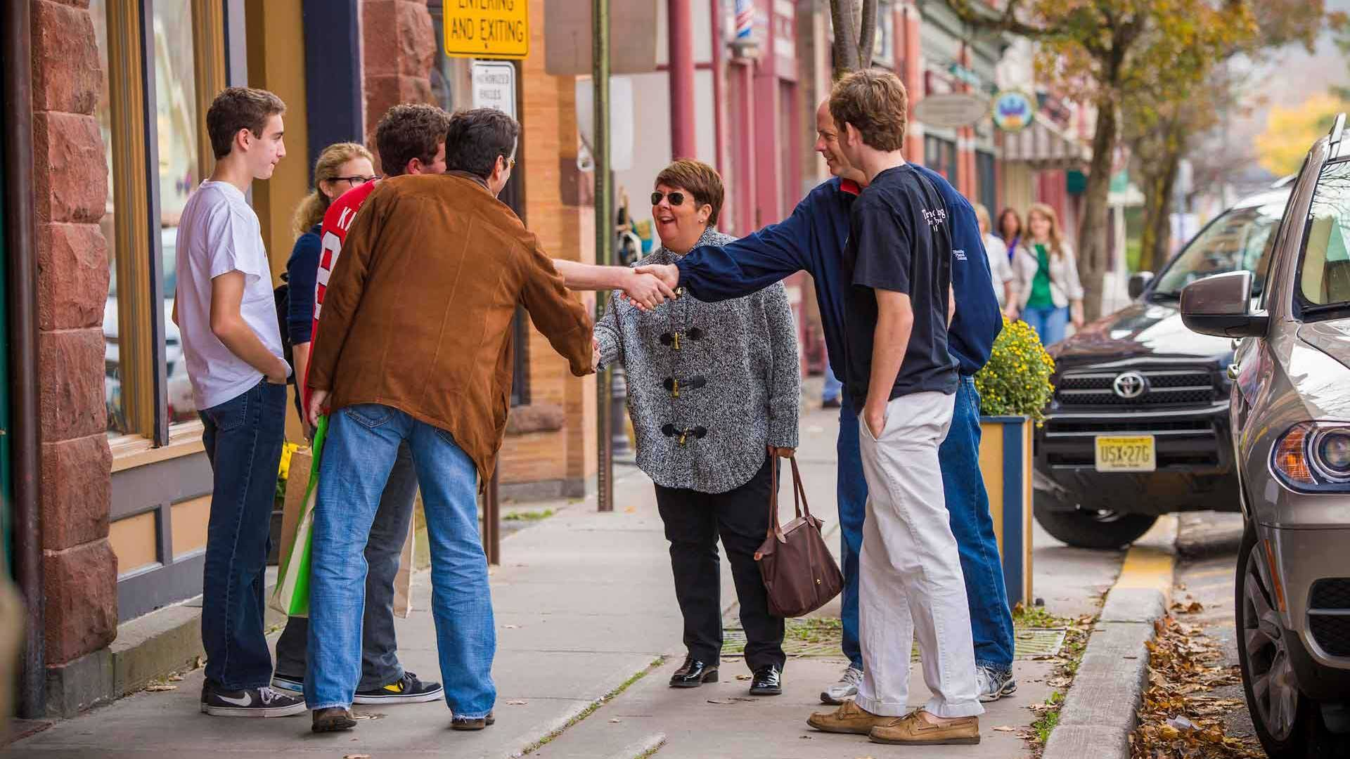 Two families greet one another and shake hands in downtown Hamilton