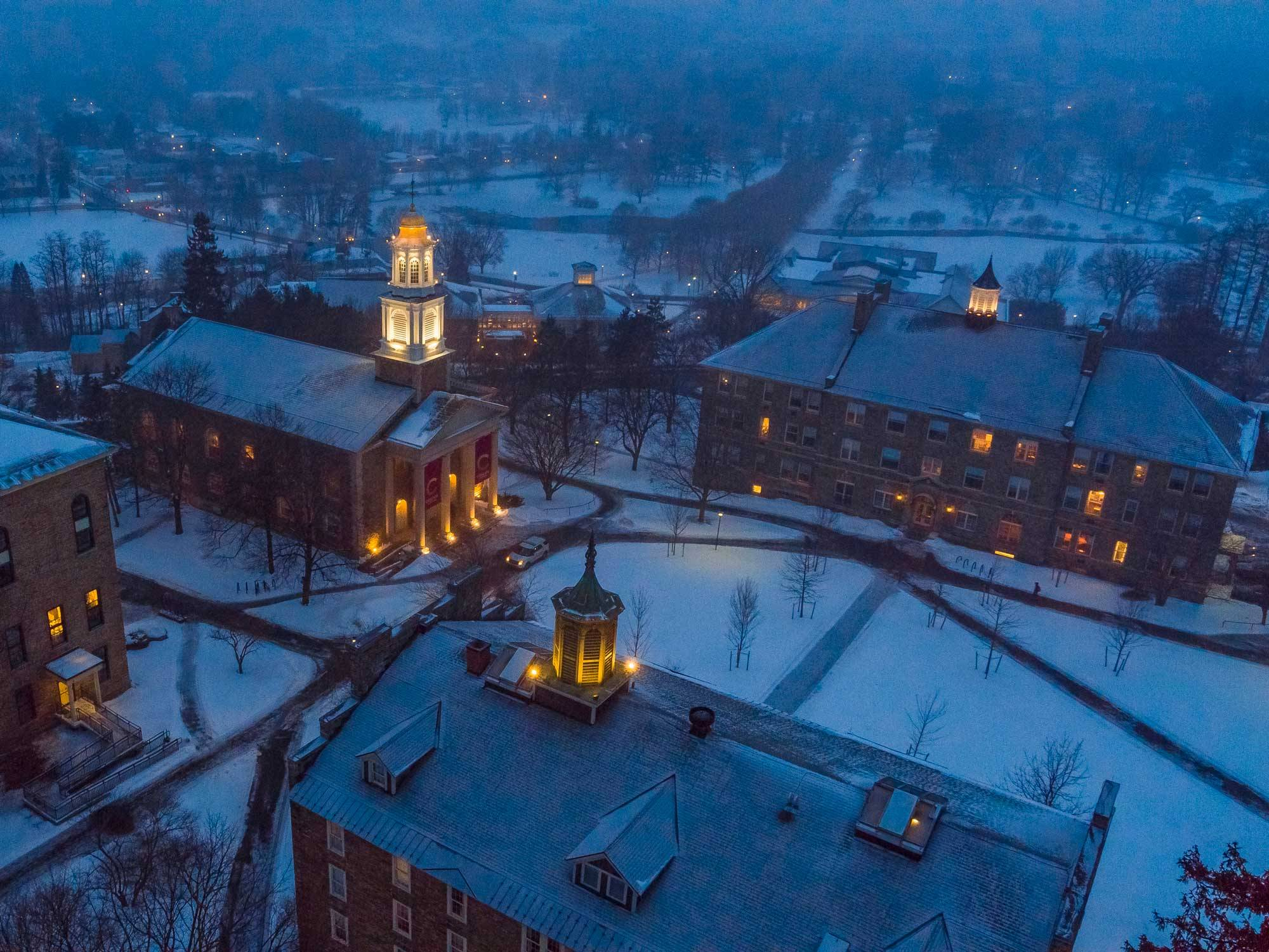 Campus buildings at dusk with snow on ground