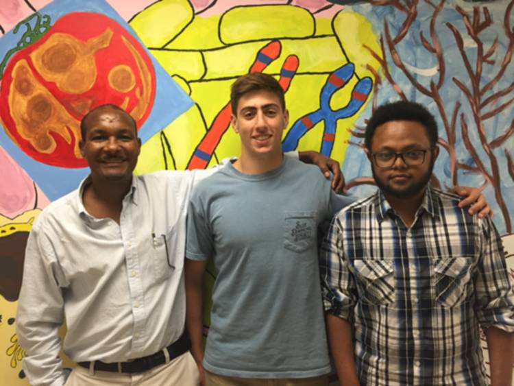 Professor and students standing in front of biology mural