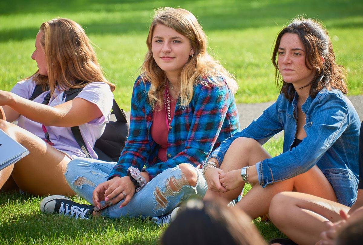 Students sitting in the grass during orientation