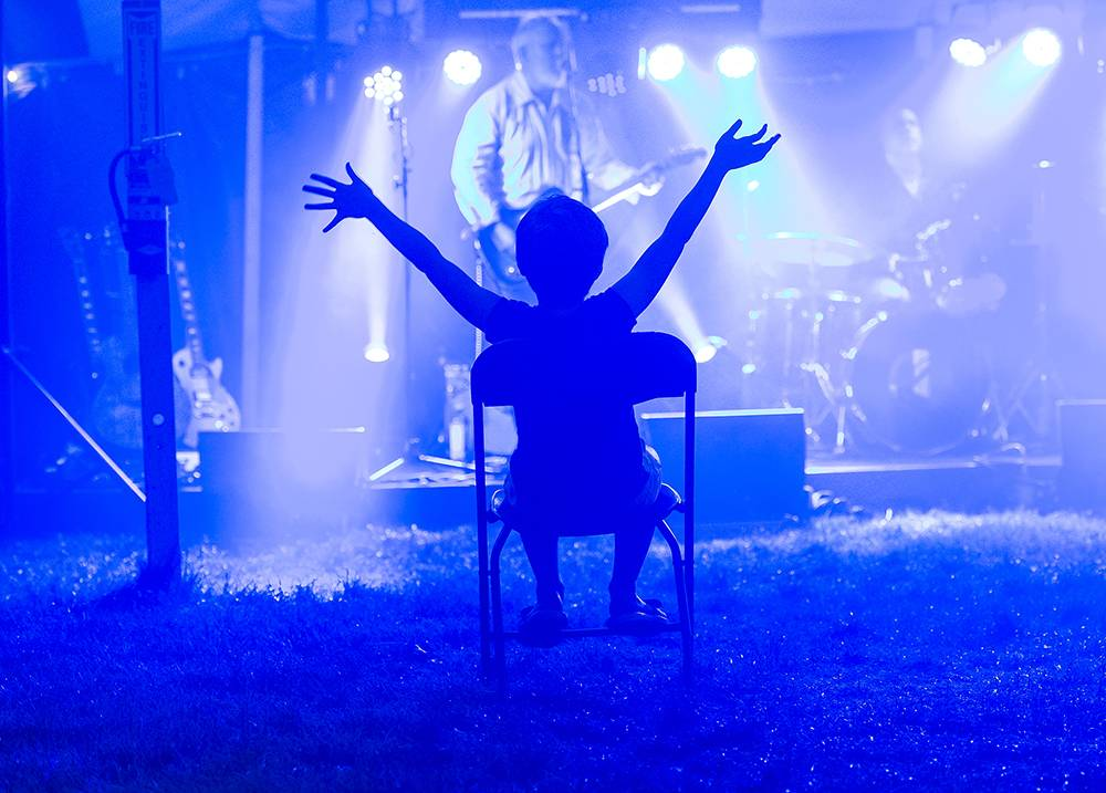 A child sits in a chair with arms raised at a concert during Reunion 2018