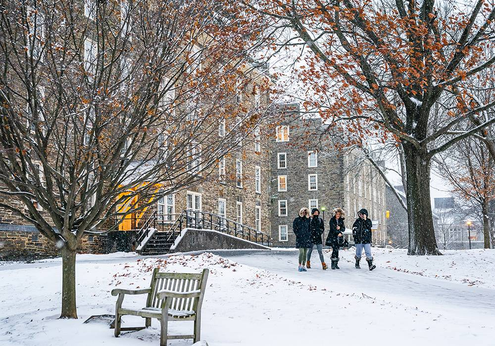 Four Colgate women walk together across the residential quad