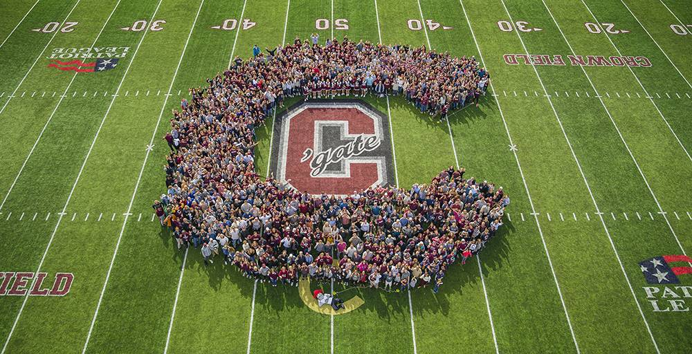 An aerial photograph of a crowd on the football field forming a large Colgate C