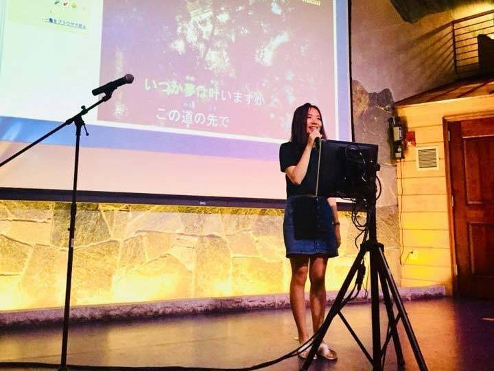 Annie Wang speaks into a mic on stage