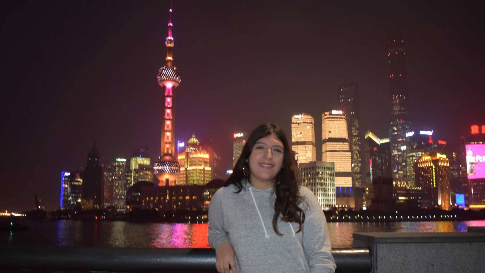 Elizabeth Gonzales in front of the illuminated Singapore skyline at night