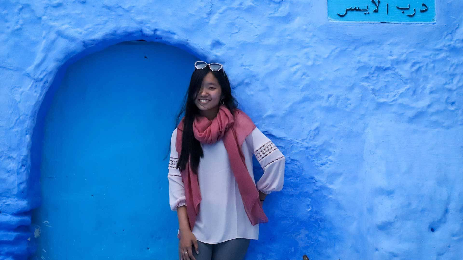 Justine Hu leans against a blue wall with a sign in Arabic on it
