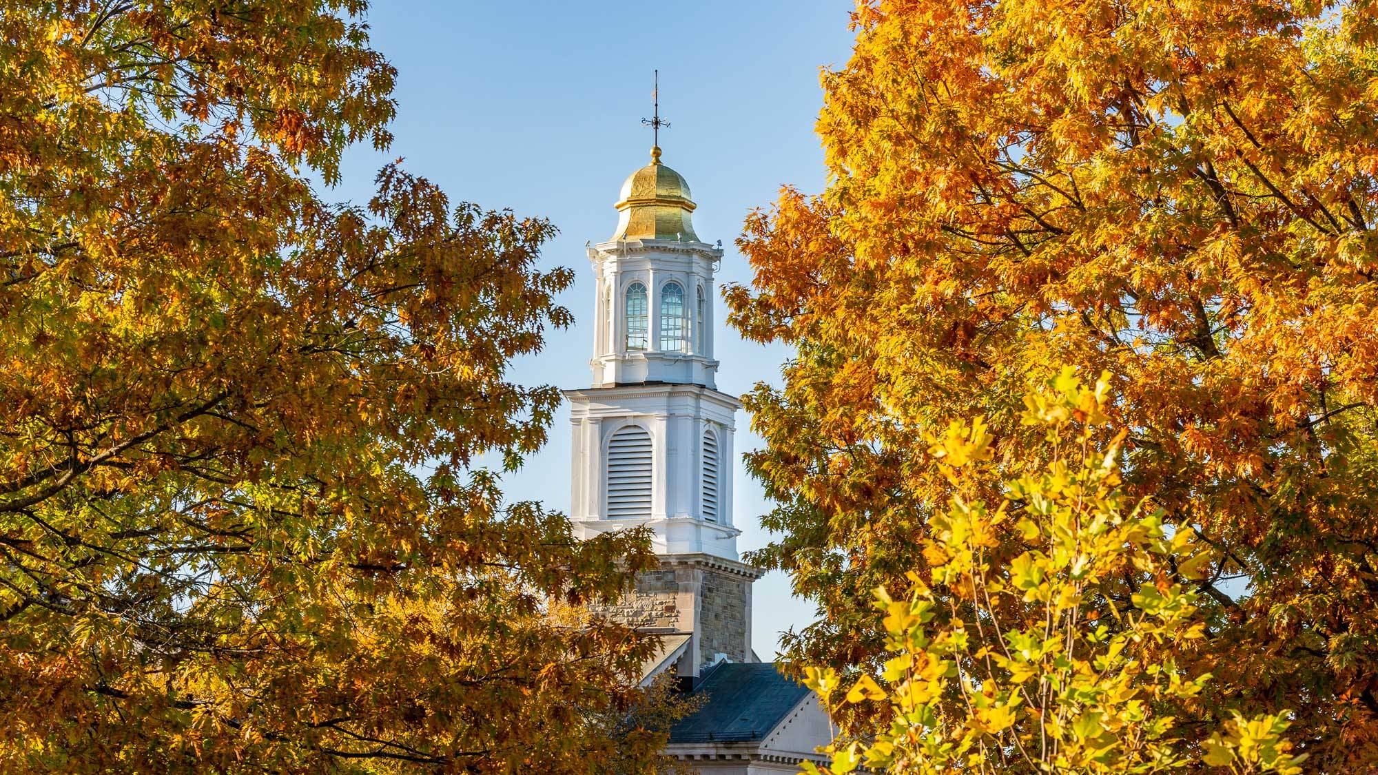 Chapel spire amid autumn foliage