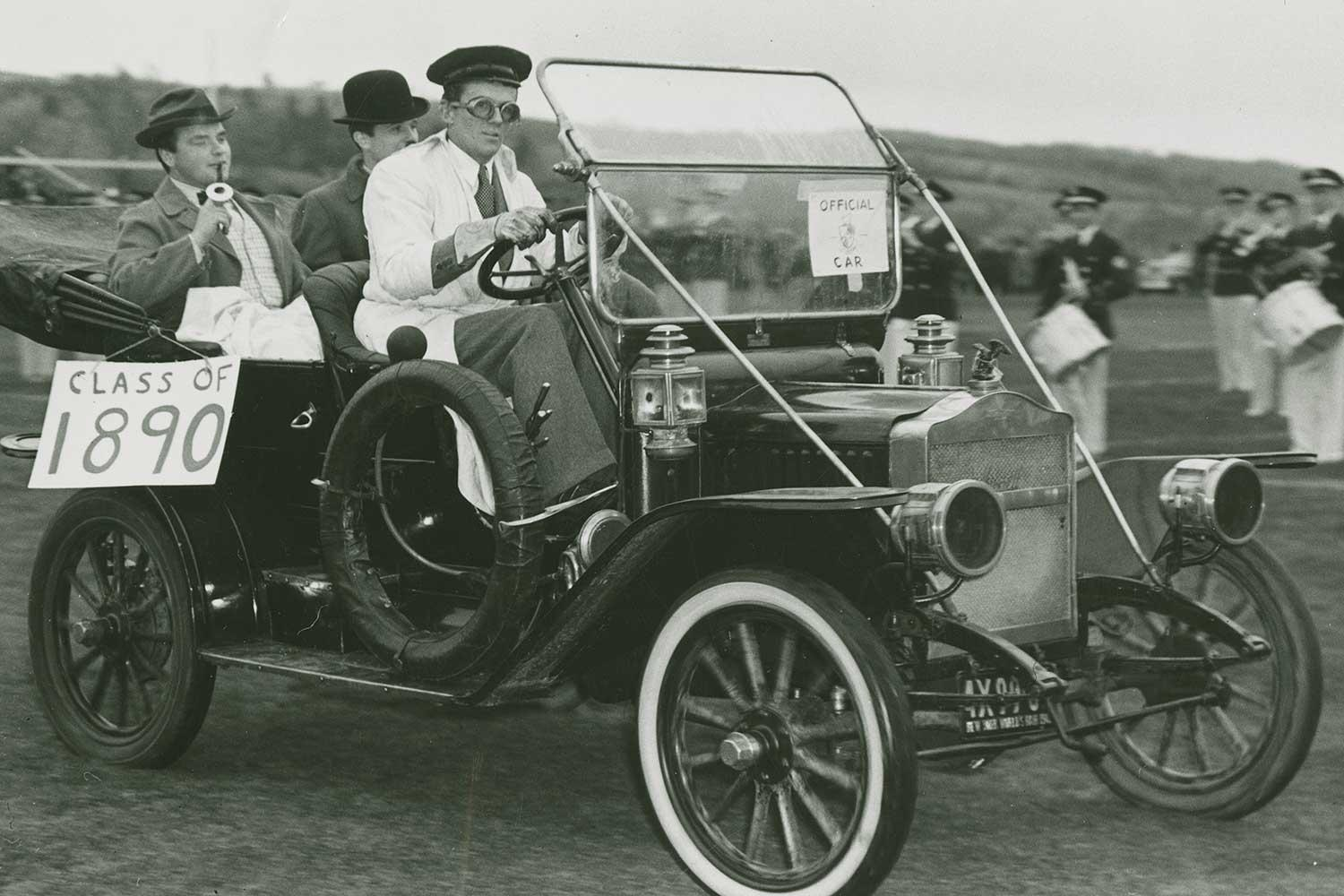 Students from the Class of 1943 driving an antique automobile