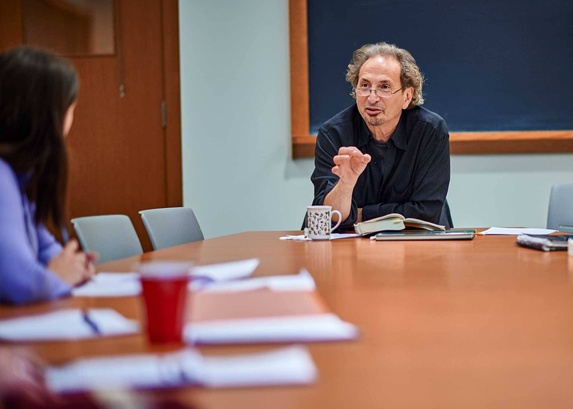 Professor Peter Balakian speaks to student while seated at a table