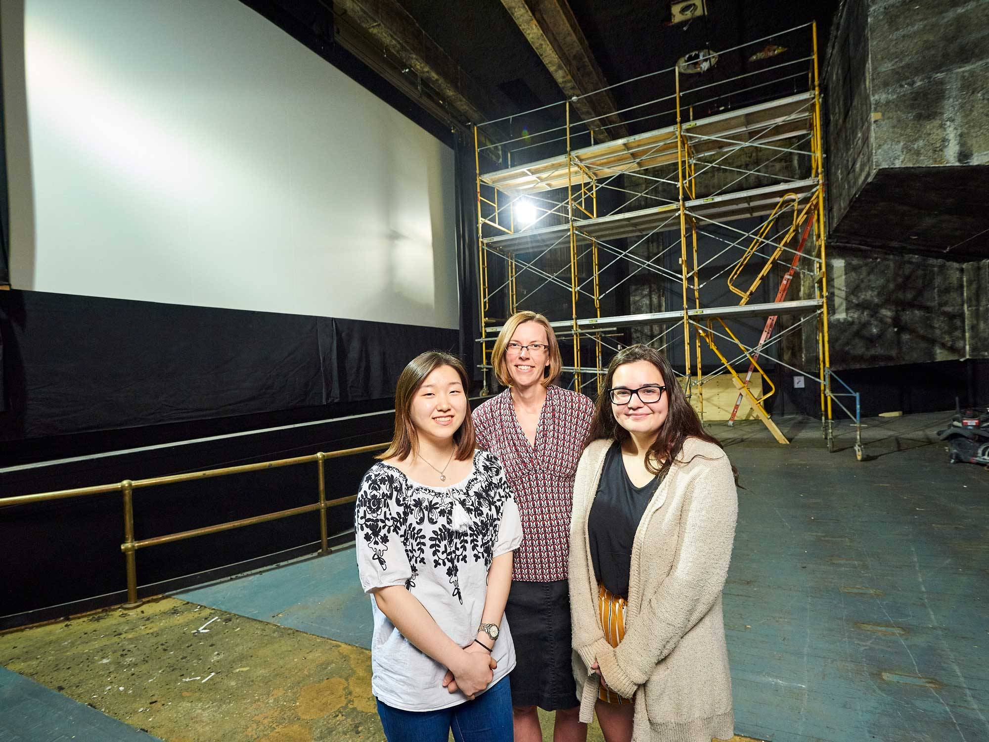 Chloe You '22, Associate Professor Mary Simonson, and Molly Adelman '21 stand in the Hamilton Theater during its renovation