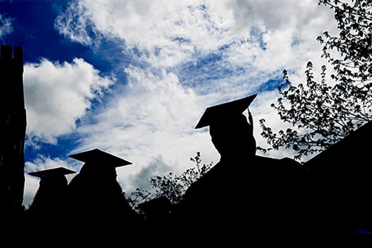 Silhouettes of students wearing graduation caps